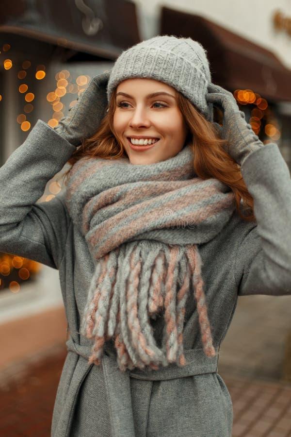 Ευτυχές όμορφο νέο κορίτσι με ένα χαμόγελο σε ένα γκρίζο καθιερώνον τη μόδα παλτό στοκ εικόνα