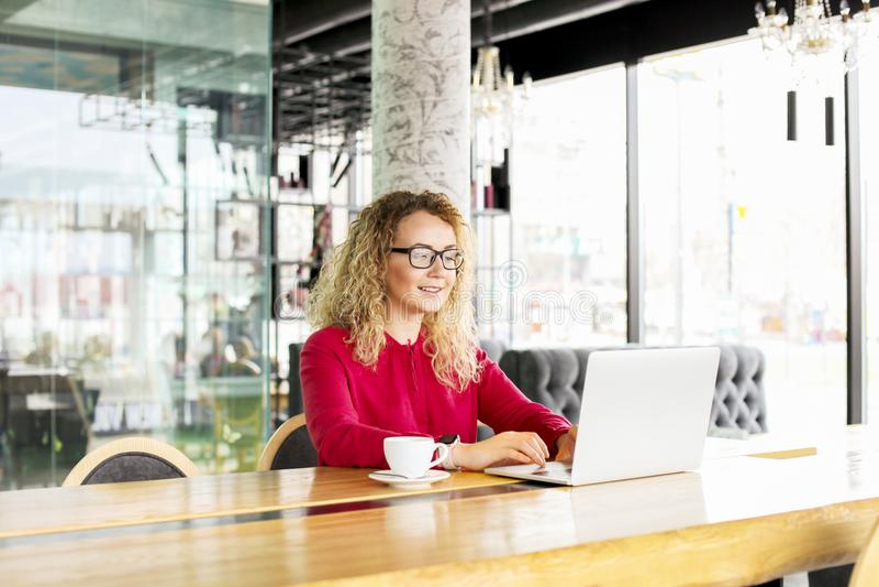 Ευτυχές όμορφο σγουρό ξανθό νέο θηλυκό τρίχας στη καφετερία που χρησιμοποιεί το lap-top, χαμόγελο Νέα ελκυστική γυναίκα freelance στοκ φωτογραφίες