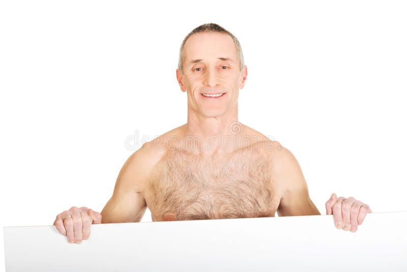 Ευτυχές ώριμο άτομο γυμνοστήθων που κρατά το κενό έμβλημα στοκ φωτογραφία