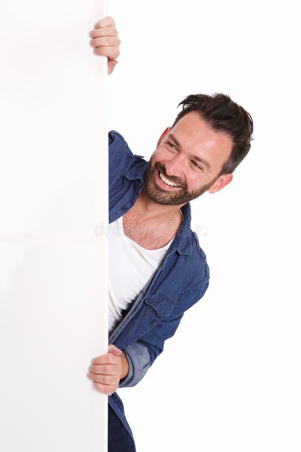 Ευτυχές ώριμο άτομο που κρυφοκοιτάζει πέρα από το κενό σημάδι αφισών στοκ φωτογραφία με δικαίωμα ελεύθερης χρήσης