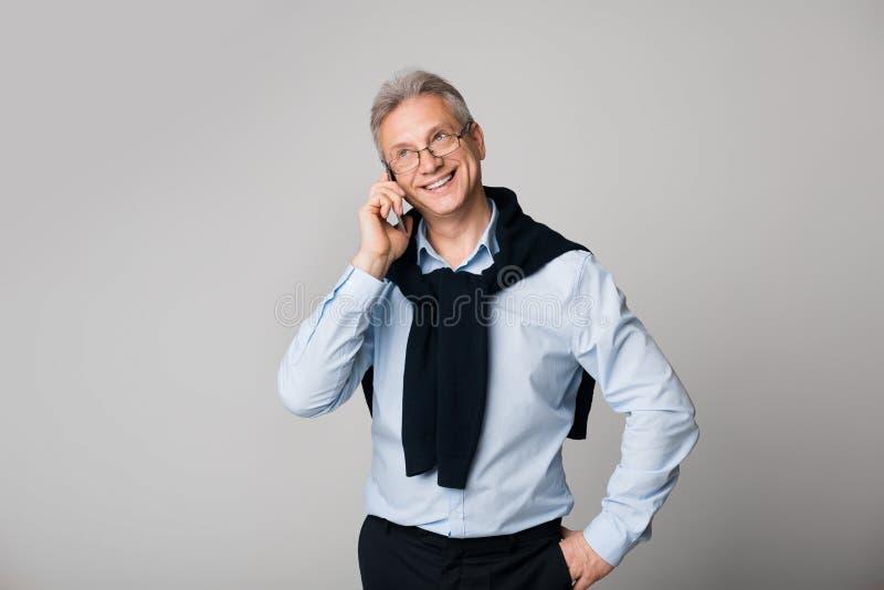 Ευτυχές ώριμο άτομο που μιλά στο τηλέφωνο πέρα από το υπόβαθρο στοκ εικόνες με δικαίωμα ελεύθερης χρήσης