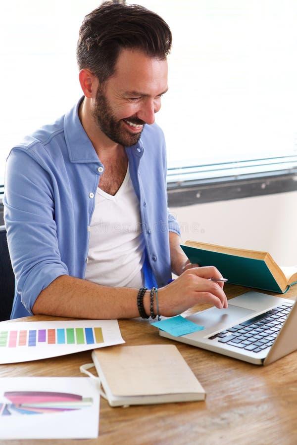 Ευτυχές ώριμο επιχειρησιακό άτομο που εργάζεται στο lap-top στο γραφείο του στοκ φωτογραφία