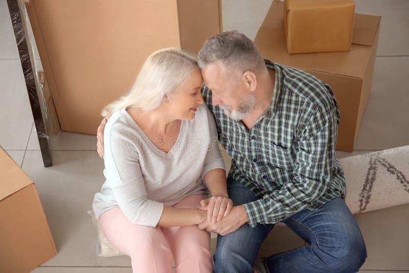 Ευτυχές ώριμο ζεύγος με τις περιουσίες που κάθεται στο πάτωμα στο εσωτερικό Κίνηση στο καινούργιο σπίτι στοκ εικόνες με δικαίωμα ελεύθερης χρήσης