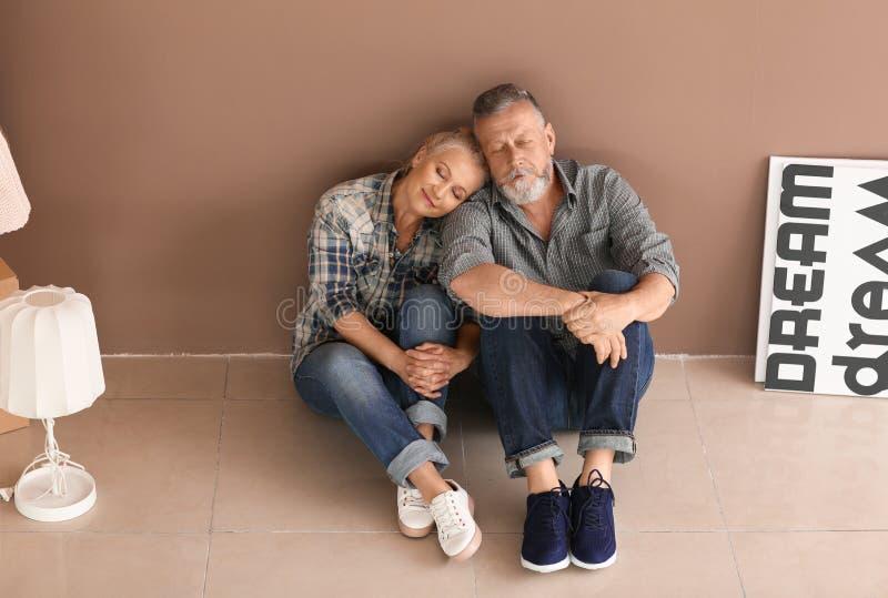 Ευτυχές ώριμο ζεύγος με τις περιουσίες που κάθεται στο πάτωμα στο εσωτερικό Κίνηση στο καινούργιο σπίτι στοκ φωτογραφίες με δικαίωμα ελεύθερης χρήσης