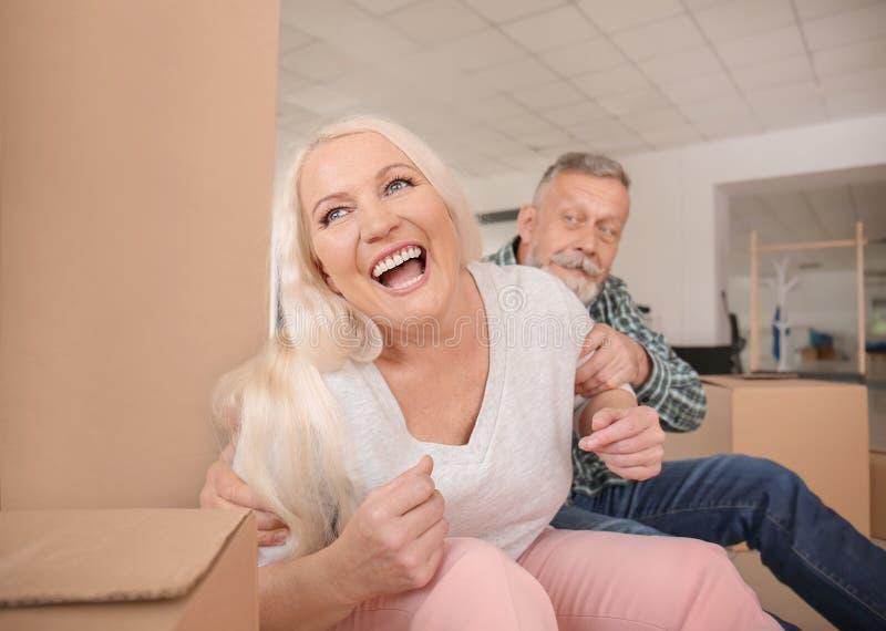 Ευτυχές ώριμο ζεύγος με τις περιουσίες στο εσωτερικό Κίνηση στο καινούργιο σπίτι στοκ φωτογραφία