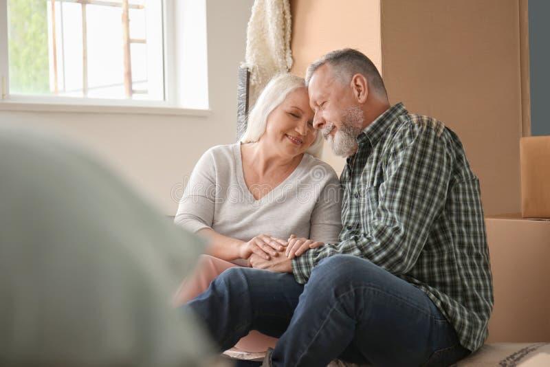 Ευτυχές ώριμο ζεύγος με τις περιουσίες στο εσωτερικό Κίνηση στο καινούργιο σπίτι στοκ εικόνα με δικαίωμα ελεύθερης χρήσης