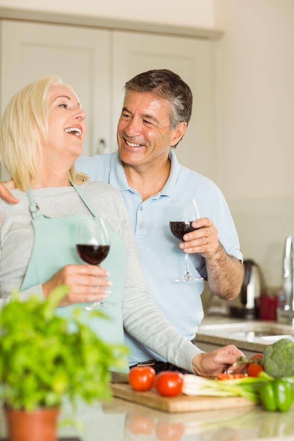 Ευτυχές ώριμο ζεύγος που έχει το κόκκινο κρασί κάνοντας το γεύμα στοκ φωτογραφία με δικαίωμα ελεύθερης χρήσης