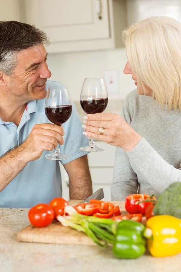 Ευτυχές ώριμο ζεύγος που έχει το κόκκινο κρασί κάνοντας το γεύμα στοκ εικόνες