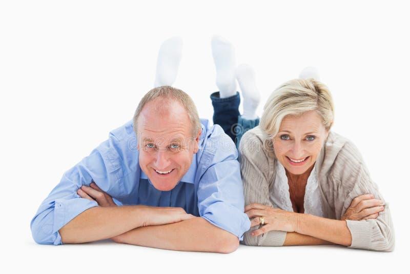 Ευτυχές ώριμο ζεύγος που βρίσκεται και που χαμογελά στοκ εικόνα με δικαίωμα ελεύθερης χρήσης