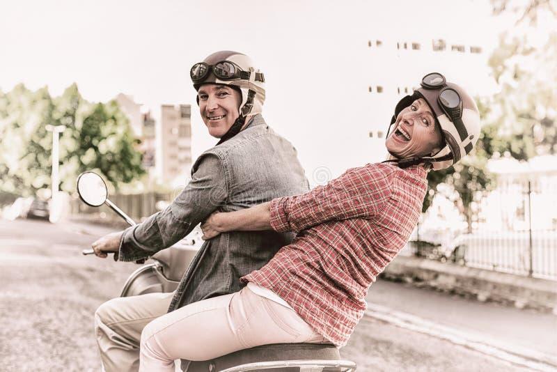 Ευτυχές ώριμο ζεύγος που οδηγά ένα μηχανικό δίκυκλο στην πόλη στοκ εικόνες