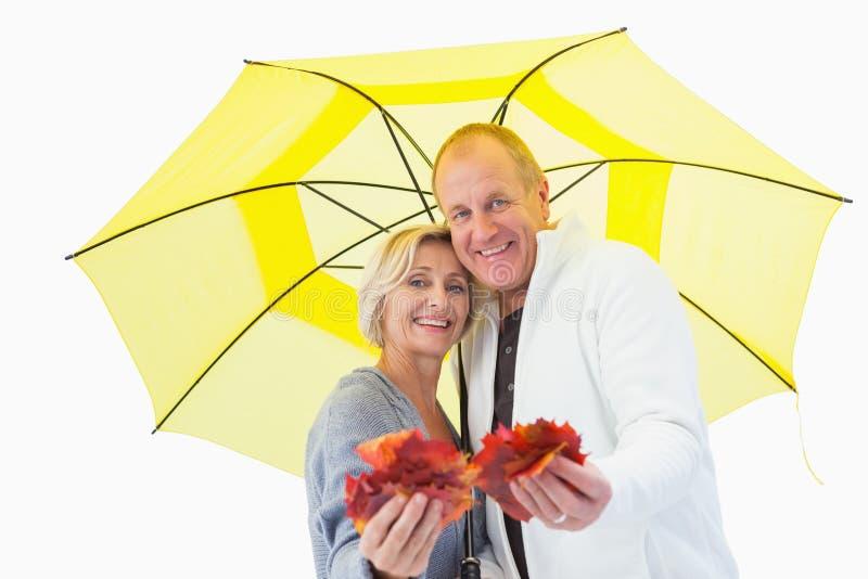 Ευτυχές ώριμο ζεύγος που παρουσιάζει φύλλα φθινοπώρου κάτω από την ομπρέλα στοκ φωτογραφία με δικαίωμα ελεύθερης χρήσης