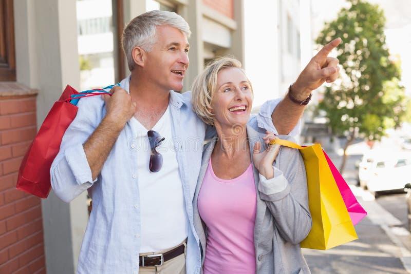 Ευτυχές ώριμο ζεύγος που περπατά με τις αγορές αγορών τους στοκ φωτογραφία με δικαίωμα ελεύθερης χρήσης