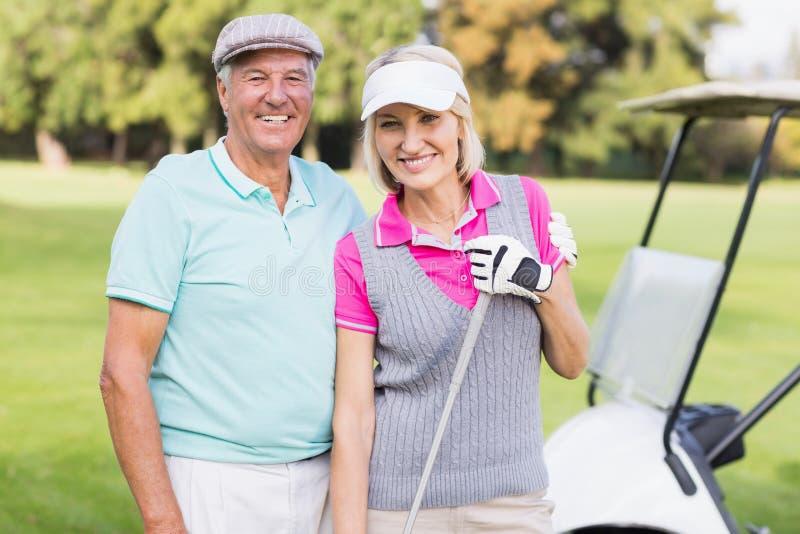 Ευτυχές ώριμο ζεύγος που στέκεται στο γήπεδο του γκολφ στοκ φωτογραφία με δικαίωμα ελεύθερης χρήσης