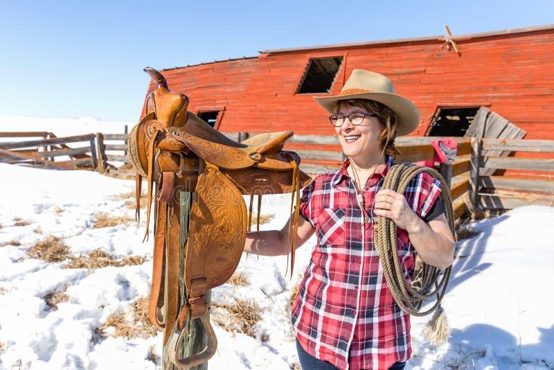 Ευτυχές cowgirl που στέκεται δίπλα στη σέλα της που κρατά ένα σχοινί στοκ εικόνα με δικαίωμα ελεύθερης χρήσης