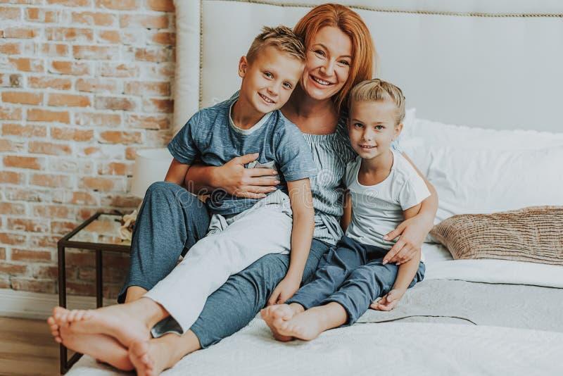 Ευτυχές mom και δύο παιδιά που χαλαρώνουν στο κρεβάτι στοκ εικόνες