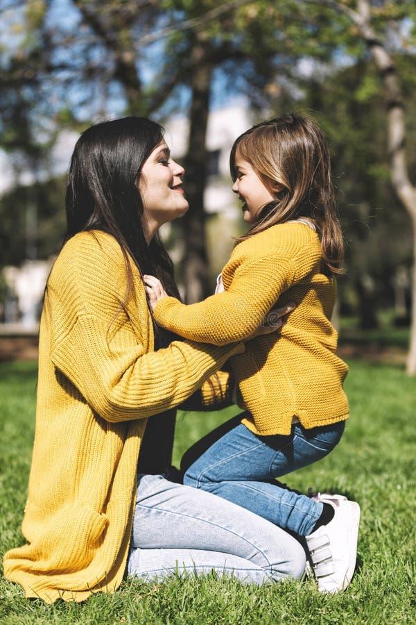 Ευτυχές mom που αγκαλιάζει την λίγη συνεδρίαση κορών τη θερινή ημέρα χορτοταπήτων στοκ εικόνες με δικαίωμα ελεύθερης χρήσης