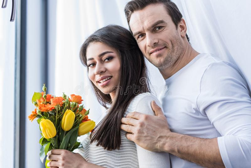 ευτυχές multiethnic ζεύγος που αγκαλιάζει και που χαμογελά στη κάμερα ενώ γυναίκα στοκ φωτογραφία