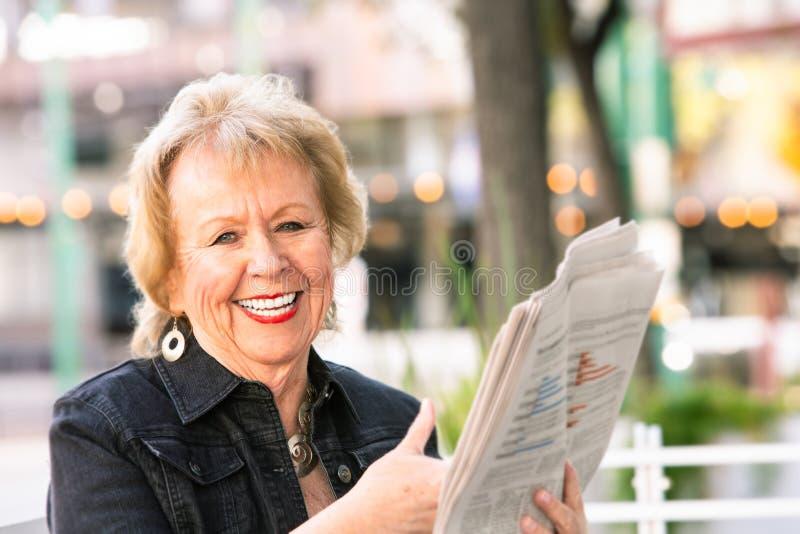 Ευτυχές Womn που αντιδρά στη αναφορά σε εφημερίδα στοκ εικόνες