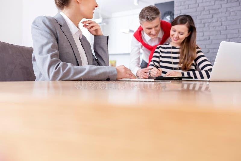 Ευτυχής άνδρας που εξετάζει τη γυναίκα που υπογράφει τη σύμβαση καθμένος με το θηλυκό realtor στον πίνακα στο διαμέρισμα στοκ εικόνες