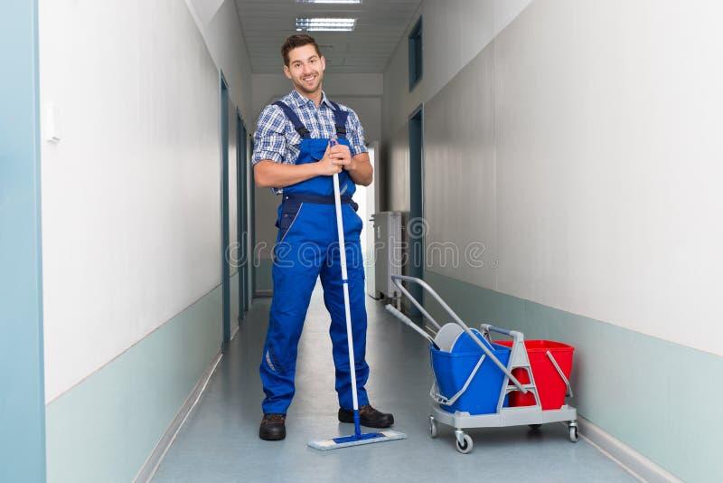Ευτυχής άνδρας εργαζόμενος με τον καθαρίζοντας διάδρομο γραφείων σκουπών στοκ φωτογραφία με δικαίωμα ελεύθερης χρήσης