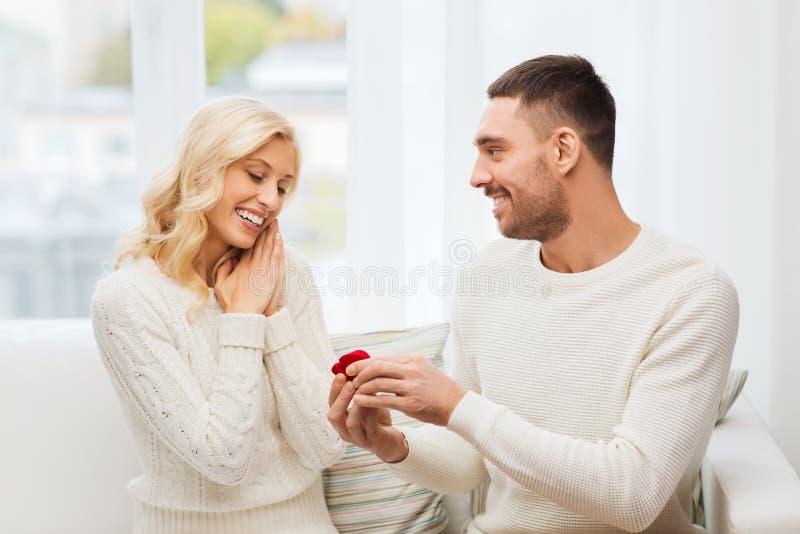 Ευτυχής άνδρας που δίνει το δαχτυλίδι αρραβώνων στη γυναίκα στο σπίτι στοκ φωτογραφία
