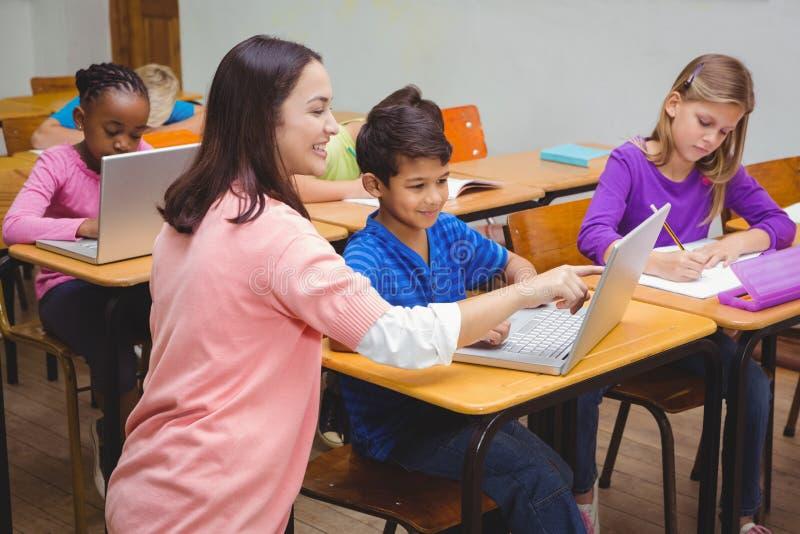 Ευτυχής δάσκαλος που χρησιμοποιεί το lap-top με το σπουδαστή στοκ φωτογραφίες με δικαίωμα ελεύθερης χρήσης