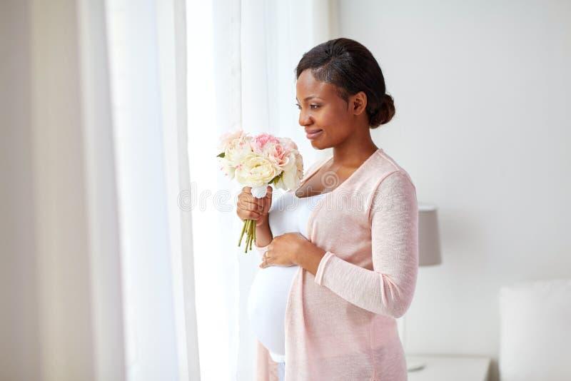 Ευτυχής έγκυος γυναίκα αφροαμερικάνων με τα λουλούδια στοκ εικόνες