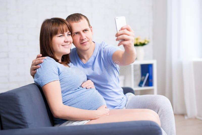 Ευτυχής έγκυος γυναίκα και ο σύζυγός της που παίρνουν selfie τη φωτογραφία με το sm στοκ φωτογραφία