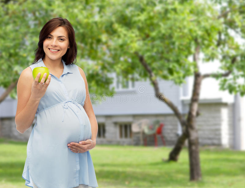 Ευτυχής έγκυος γυναίκα που κρατά το πράσινο μήλο στοκ φωτογραφίες με δικαίωμα ελεύθερης χρήσης