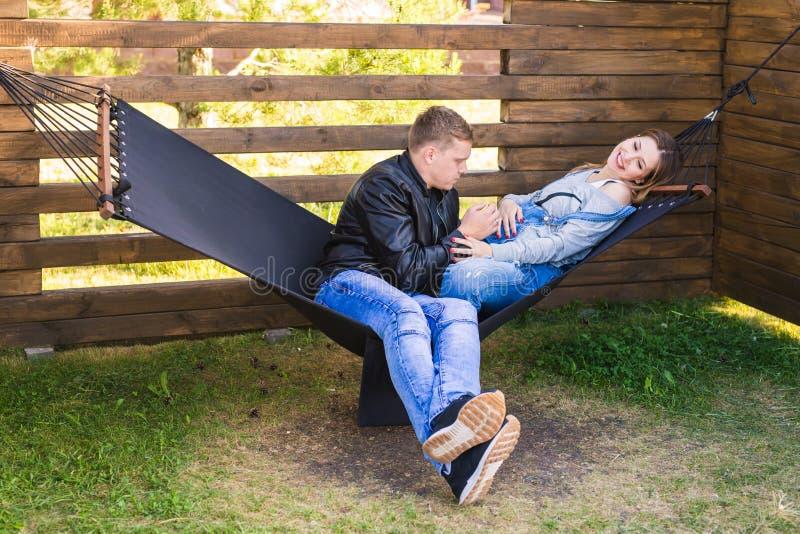 Ευτυχής έγκυος συνεδρίαση ζευγών στην αιώρα - έννοια οικογενειών, πατρότητας και ευτυχίας στοκ φωτογραφία με δικαίωμα ελεύθερης χρήσης
