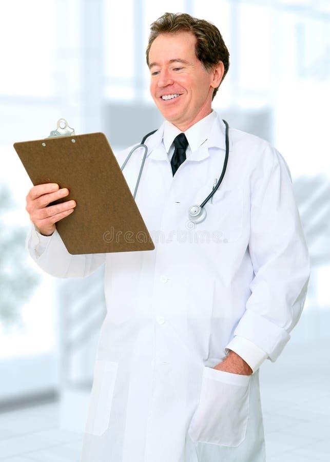 Ευτυχής έκθεση ανάγνωσης γιατρών χαμόγελου στο γραφείο του στοκ φωτογραφίες