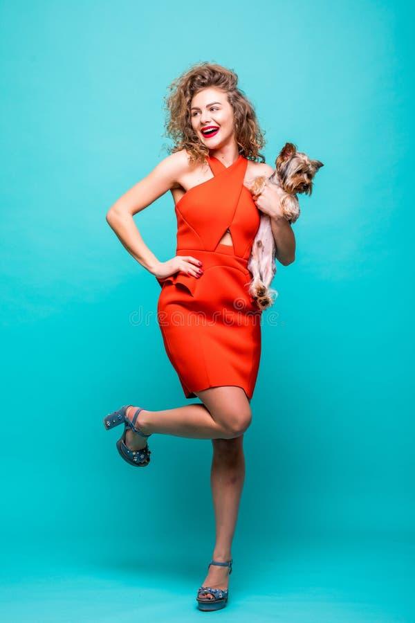 Ευτυχής ένδυση κοριτσιών στο κόκκινο αγκάλιασμα φορεμάτων και τοποθέτηση με το καλό σκυλί τεριέ του Γιορκσάιρ της που απομονώνετα στοκ φωτογραφίες