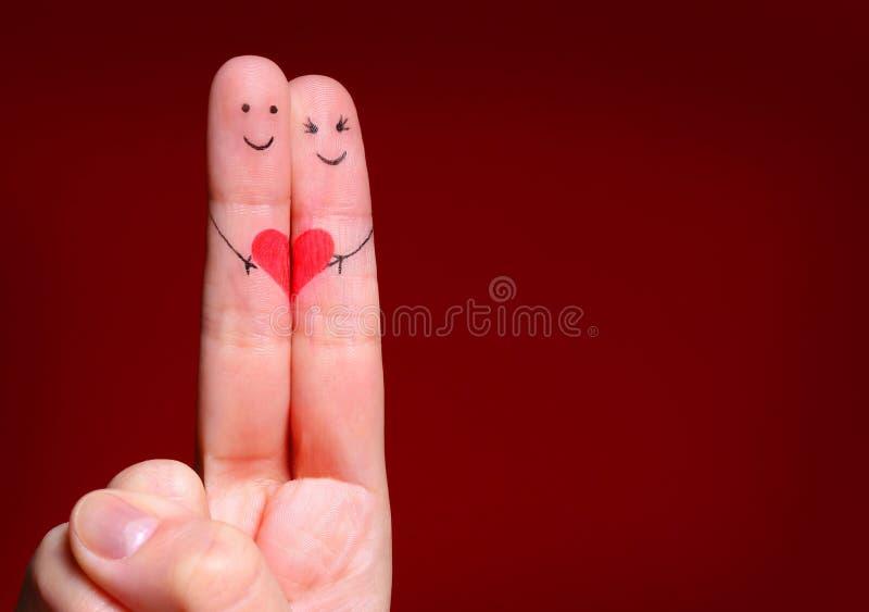 Ευτυχής έννοια ζεύγους. Δύο δάχτυλα ερωτευμένα με το χρωματισμένο χαμόγελο στοκ φωτογραφία