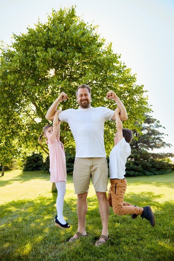 Ευτυχής ένωση αγοριών και κοριτσιών στους μυς του πατέρα στοκ εικόνα με δικαίωμα ελεύθερης χρήσης