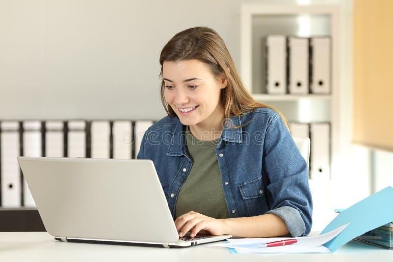 Ευτυχής έφηβος οικότροφων που εργάζεται στο γραφείο στοκ εικόνες