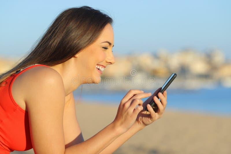 Ευτυχής έφηβος που ψάχνει στο έξυπνο τηλέφωνο στην παραλία στοκ εικόνα