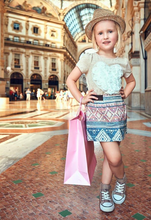 Ευτυχής λίγος έμπορος μόδας με τη ρόδινη τσάντα αγορών σε Galleria στοκ φωτογραφίες