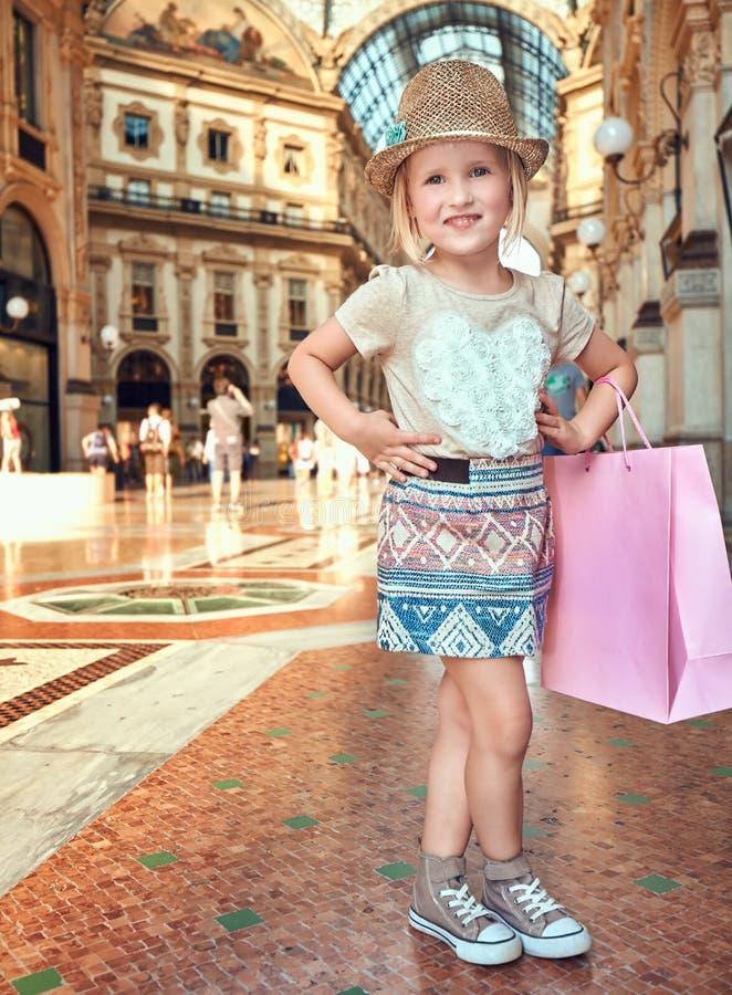 Ευτυχής λίγος έμπορος μόδας με τη ρόδινη τσάντα αγορών σε Galleria στοκ εικόνες με δικαίωμα ελεύθερης χρήσης