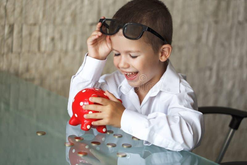 Ευτυχής λίγο αγόρι διευθυντών με τα νομίσματα και piggy τράπεζα στοκ φωτογραφία με δικαίωμα ελεύθερης χρήσης