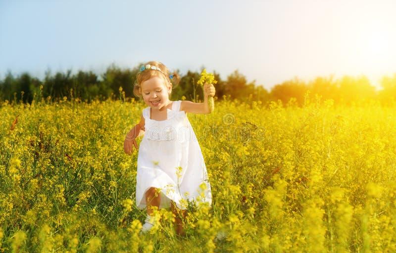 Ευτυχής λίγο κορίτσι παιδιών που τρέχει στον τομέα με τα κίτρινα λουλούδια στοκ εικόνες