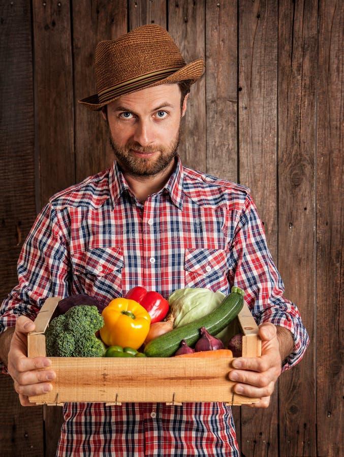 Ευτυχής αγρότης που κρατά το ξύλινο κιβώτιο των λαχανικών στοκ εικόνες