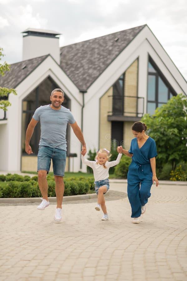 Ευτυχής ακτινοβολώντας οικογένεια που πηδά και που τρέχει περπατώντας στοκ εικόνες
