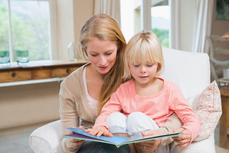 Ευτυχής ανάγνωση μητέρων και κορών από κοινού στοκ εικόνα
