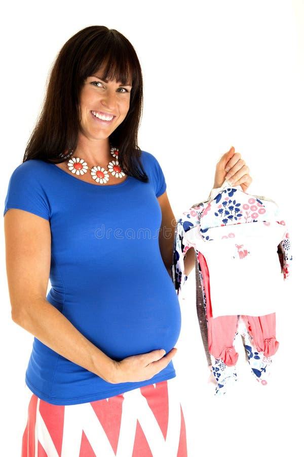Ευτυχής αναμένουσα μητέρα που κρατά τα νέα ενδύματα μωρών κοριτσιών στοκ εικόνα