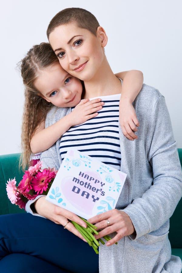 Ευτυχής ανασκόπηση ημέρας μητέρων ` s Χαριτωμένο μικρό κορίτσι που αγκαλιάζει mom μετά από να δώσει την κάρτα ημέρας μητέρων της στοκ φωτογραφία με δικαίωμα ελεύθερης χρήσης