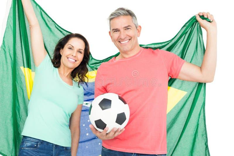 Ευτυχής ανεμιστήρας ζευγών της σημαίας της Βραζιλίας εκμετάλλευσης ποδοσφαίρου στοκ εικόνες