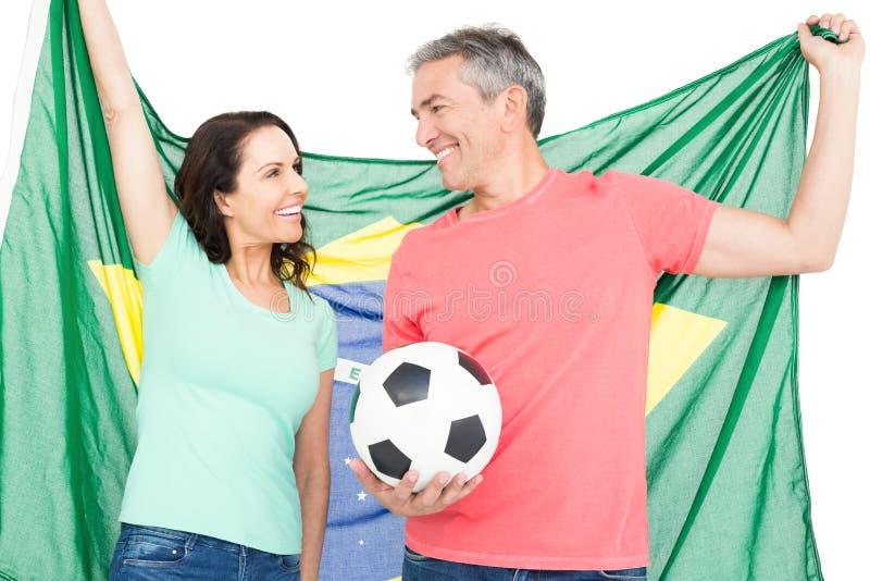 Ευτυχής ανεμιστήρας ζευγών της σημαίας της Βραζιλίας εκμετάλλευσης ποδοσφαίρου στοκ φωτογραφίες