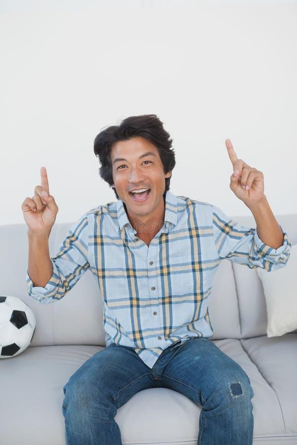 Ευτυχής ανεμιστήρας ποδοσφαίρου ενθαρρυντικός προσέχοντας τη TV στοκ φωτογραφία