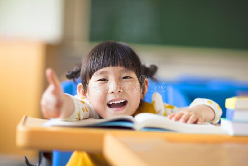 Ευτυχής αντίχειρας παιδιών επάνω με το βιβλίο στοκ εικόνα με δικαίωμα ελεύθερης χρήσης