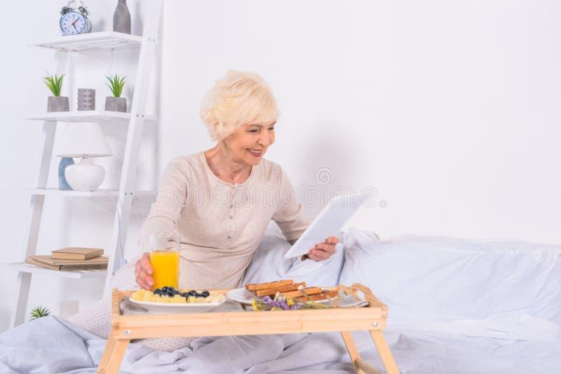 ευτυχής ανώτερη γυναίκα με το πρόγευμα στο κρεβάτι που χρησιμοποιεί την ταμπλέτα στοκ φωτογραφίες